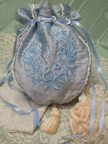 100% Silk ribbon drawstring feeds through mother of pearl circlets Fully lined in soft blue satin 4-panel purse features ivory piping and blue floral embroidery Ivory Tassel 9 1/2 x 7 1/2