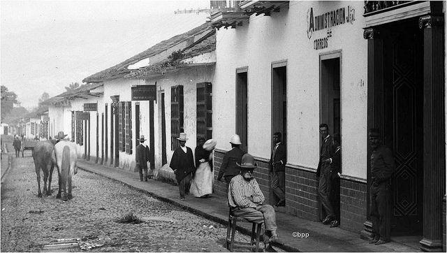 Cosiaca sentado parsimoniosamente en un taburete en plena calle Calibío, frente a la Casa de Gobierno de Antioquia (en el sitio donde está hoy el Palacio de la Cultura Rafael Uribe Uribe)  Fotografiado por Melitón Rodríguez Márquez en 1900
