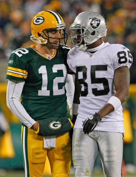Green Bay Packers quarterback Aaron Rodgers #12 and Oakland Raiders wide receiver Darrius Heyward-Bey #85 exchange words during a time out.