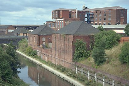SANDWELL MB SPON LANE SOUTH SP 08 NW Smethwick 9/133 Two warehouses, immediately east of Canal Bridge, 21.7.78 Chance's Glassworks GV II Warehouses. Circa 1853. Brick with hipped slate roofs. Both adjoin the Birmingham Level of the Birmingham Canal and rise above the brick retaining wall of the canal cutting. Both are of similar dimensions and are linked by a low brick wall. The western warehouse has four tall blocked openings facing the canal, with segmental heads. The wall of the eastern…