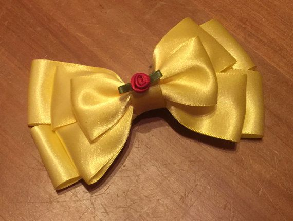 Princess Belle themed hair bow on clip. Featuring lots of yellow ribbon to give the layered look and finished with a red rose decoration. All