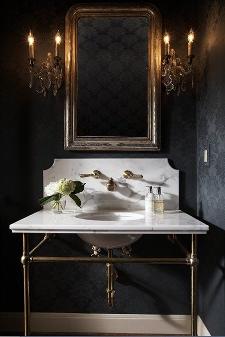 Modern and moody bathroom with black brocade wallpaper and a marble sink.