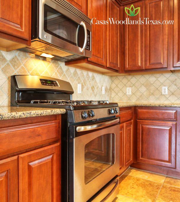 Cocina con gabinetes de madera electrodom sticos de acero - Cocinas con encimeras de granito ...
