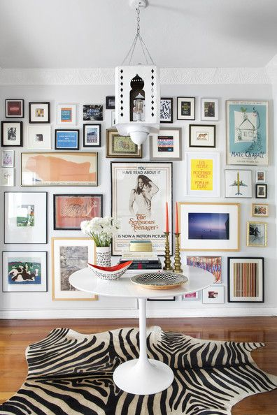 A gallery wall behind a Saarinen table on a zebra rug.  Max Humphrey, Lonny, September 2013