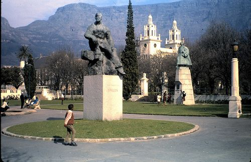 A boy looks up at a statue of Jan Smuts, the only person to sign each of the peace treaties ending the First and Second World Wars as well as a supporter of racial segregation and white minority rule, Cape Town, South Africa, 1970, photograph by All Hails.