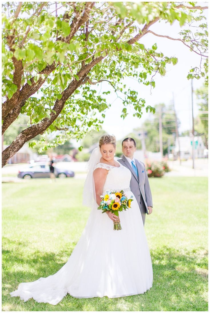 Summer church wedding in Carlinville, Illinois. Sunflower bouquet with light blue colors, ties, and bridesmaid dresses.