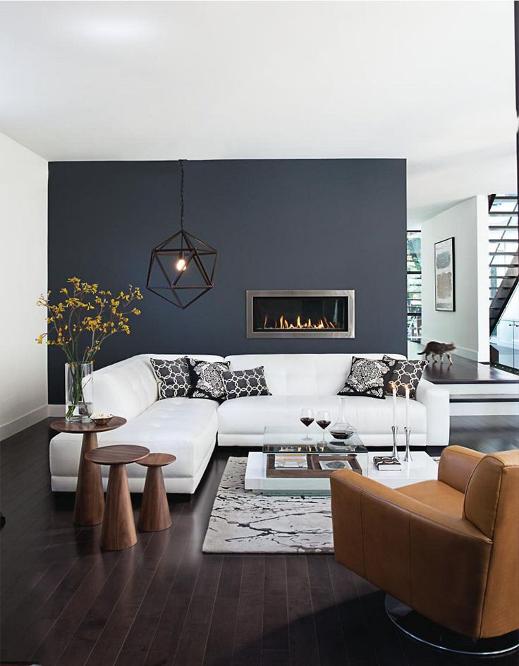 Modern living room. I love the dark wall and the fire place.