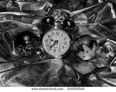 Christmas balls with an alarm clock on a black and white image