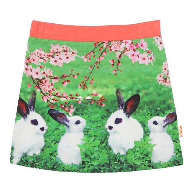 Rokje Lola Rabbits van het kinderkleding merk Wild kidswear  Een zomer rokje zonder sluiting (elastische taille), met een prachtige all over print van witte konijntjes in een groen veld onder een roze struik. De taille band is in het effen licht roos.