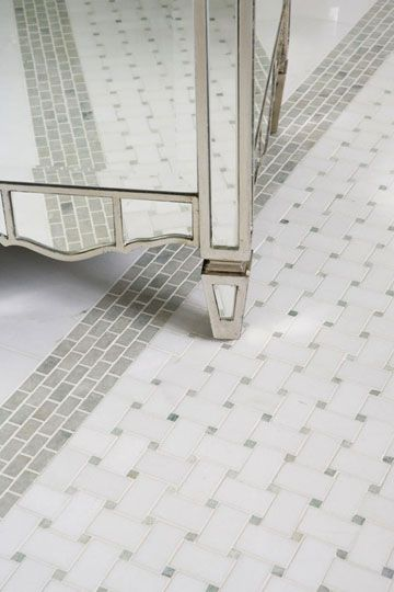"""Marble Tile Floor  The mirrored vanity stool echoes the credenza by the tub and reflects a tile """"rug"""" composed of basketweave tiles and a green border that complements the cool celadon walls and vanity backsplash."""
