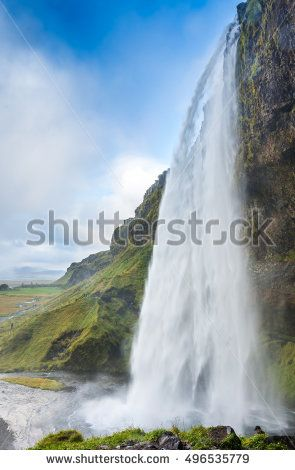 Seljalandsfoss waterfall in Southern Iceland on the road to Thorsmork.. The Seljalands River that has its origin in the Eyjafjallajokull volcano glacier drops 60 meters in front of a cave.