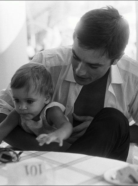 Alain Delon assis à une table avec sur les genoux son fils Anthony 11 mois au Beach de Monaco.
