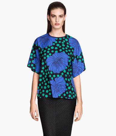 Een wijde blouse van geweven kwaliteit met een geprint dessin. De blouse heeft korte mouwen, een smal boordje langs de halsopening en een blinde ritssluiting in de nek.