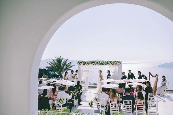 Unplugged wedding - ask your guests to be 100% present at the ceremony. They will have plenty of photos from the professionals | Luxury weddings in Santorini