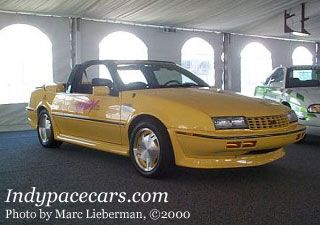 Only three 1990 Chevrolet Beretta convertibles were used in pace car duty, and were supplemented by a fleet of 30 yellow and 50 teal Corvette convertibles for parade and festival duty. The pace car was powered by a modified 3.4L V-6 engine, and the front-wheel-drive car featured a roll-bar with integrated strobe lights, as well as strobes added to the trunk face.