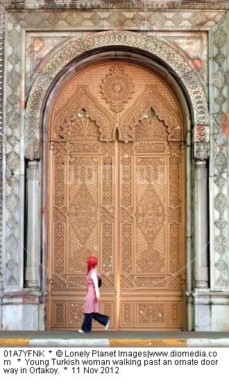 Young Turkish woman walking past an ornate doorway in Ortakoy.