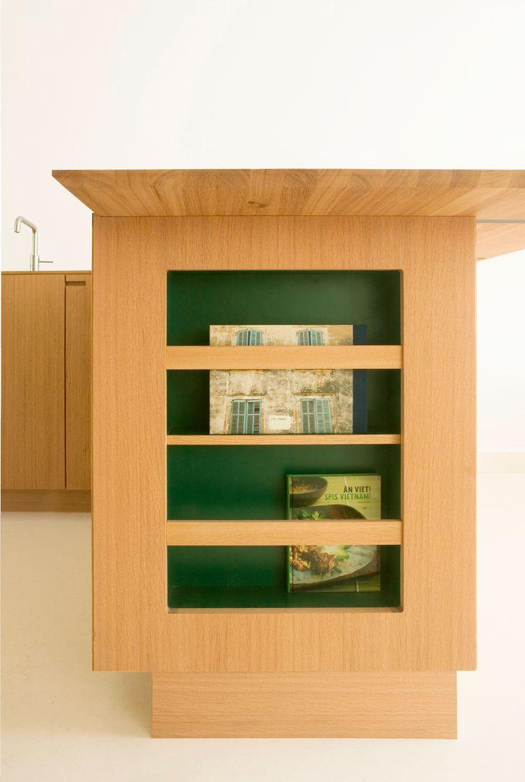 A integrated magazine rack allows for easy storage in this Copenhagen kitchen. #green #laminate #oak #wood #kitchen #scandinavian #magazine  #coffebook #interior
