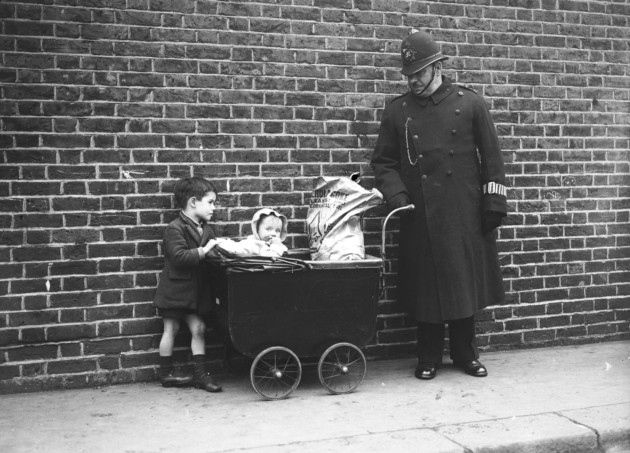 14th November 1935:  A London policeman looks after some children in Bethnal Green while their mother votes in the General Election.  (Photo by Maeers/Fox Photos/Getty Images)