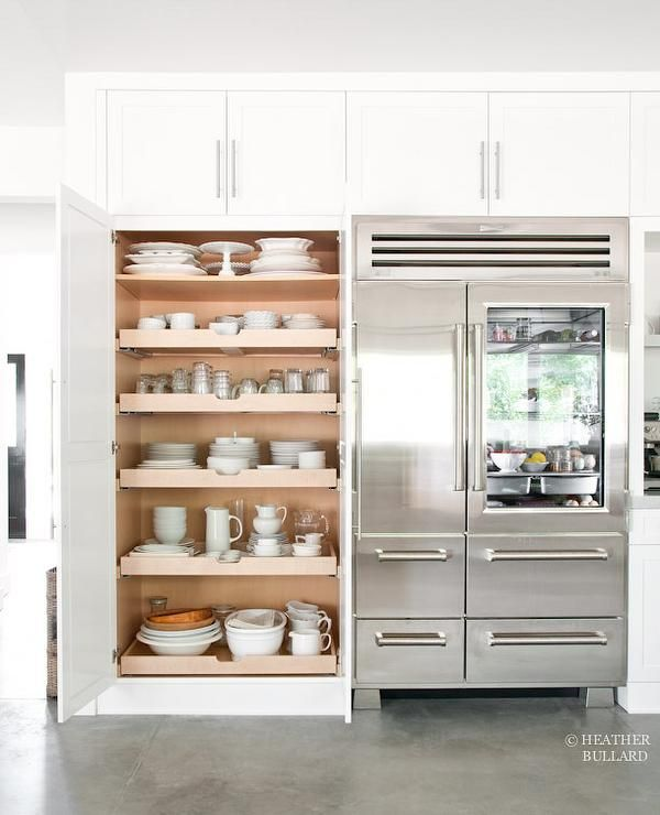Sweet cottage kitchen features a glass-front refrigerator ex to a pantry fitted with pull out shelves.