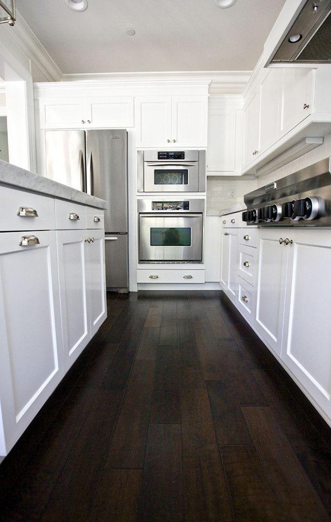 Love the dark hardwood floors in this white kitchen for White kitchen cabinets with dark hardwood floors
