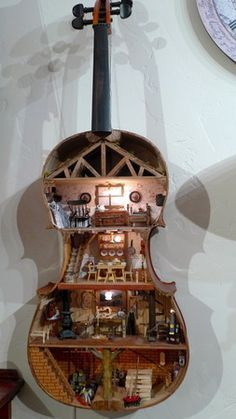 There are sooo many cool things you can do with old wooden instrument bodies. This one is quite the intricate dollhouse out of an old violin.