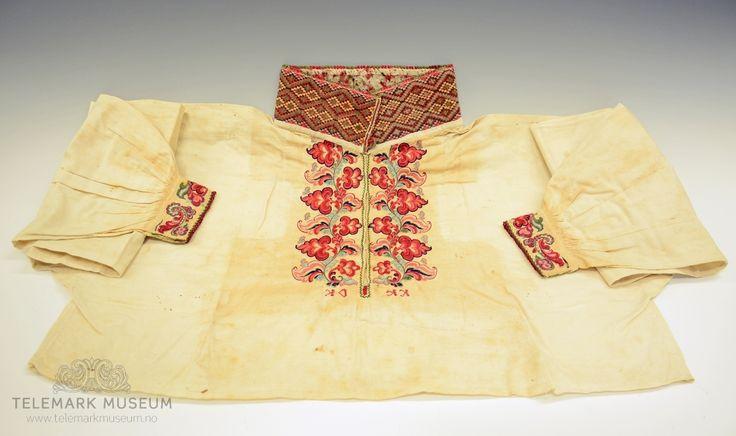 Skjorten tilhører kvinnedrakt TGM-BM.1915. A-F. Skjorte til folkdrakt sydd i primærsnitt med halslinning/kvarde og ermlinninger. Foran har skjorten broderier på hver side av åpningen. Broderiene er utført plattsøm og kontursting som danner rosesømmen. Under åpningen er det brodert initialene: KD og KK, disse er brodert speilvendt i korssting. Halskvarden er utført i korssting og med tagger av staver med stoppesøm i grønt og rødt. Hempene på hver side er røde og er sydd med knapphullsting i…