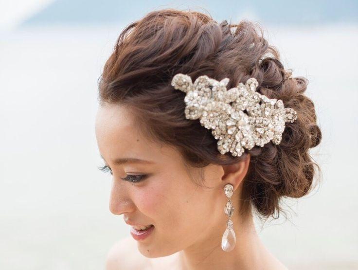 結婚式は女性のあこがれ。当日は自分の大好きなドレスを着て、素敵なヘアアレンジでゲストの前に登場したいですよね。「でもヘアアレンジを決めるのってむずかしい……」と思ってはいませんか?どんなヘアアレンジもどれもかわいくて、迷ってしまいますよね。今回はそんな花嫁サマたちのヒントになるように、現役ヘアスタイリストから、ビジューを使ったヘアアレンジをご紹介します!プリンセスのような華やかさときらびやかさを取り入れることができるビジューのヘアアレンジはすごくオススメですよ☆ ビジューへアアレンジ①上品なアップへアにゴージャスなビジューをつけて華やかさをアップ  すっきりとまとめたシンプルなアップヘアにビジューを重ね付けしてゴージャス感をプラス。上品な雰囲気に、華やかなビジューが加わりぐんときらびやかになります! ビジューへアアレンジ②キュートな雰囲気がお好きな方はビジューを高めにつけるのがポイント…