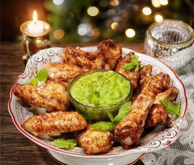 Ugnsstekta kycklingvingar med en kryddig blandning av spiskummin, paprika, cayennepeppar och koriander. Rör ihop en sval, frisk ärthummus på yogurt, gröna ärtor och mynta med vitlök att dippa i!