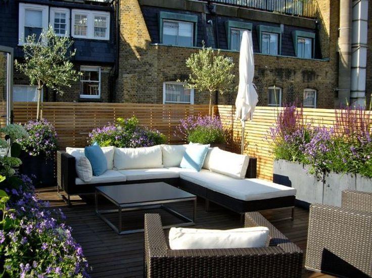salon extérieur sur le toit-terrasse avec plantes à fleurs et oliviers