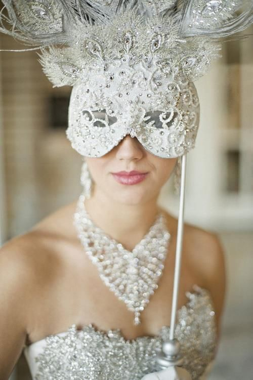 A vision in white. A gorgeous venetian mask, with embroidery, feathers and diamonds.