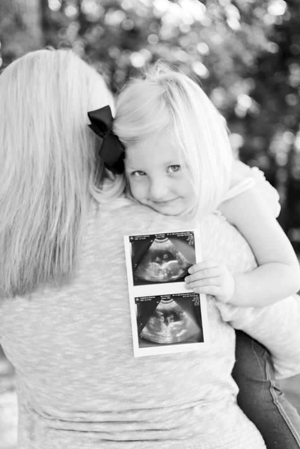 Cute maternity shot with mom holding child and child holding ultra-sound pics