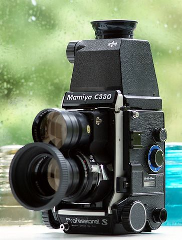 Mamiya C330  This twin-lens reflex classic camera is said to be introduced in the 1970s, by Mamiya Digital Imaging Co., Ltd. (マミヤ・デジタル・イメージングー株式会社, Mamiya Dejitaru Imejingu Kabushiki-gaisha). You can see the twin-lens connected to the camera's body: One is apparently for looking and another is for snapshots.