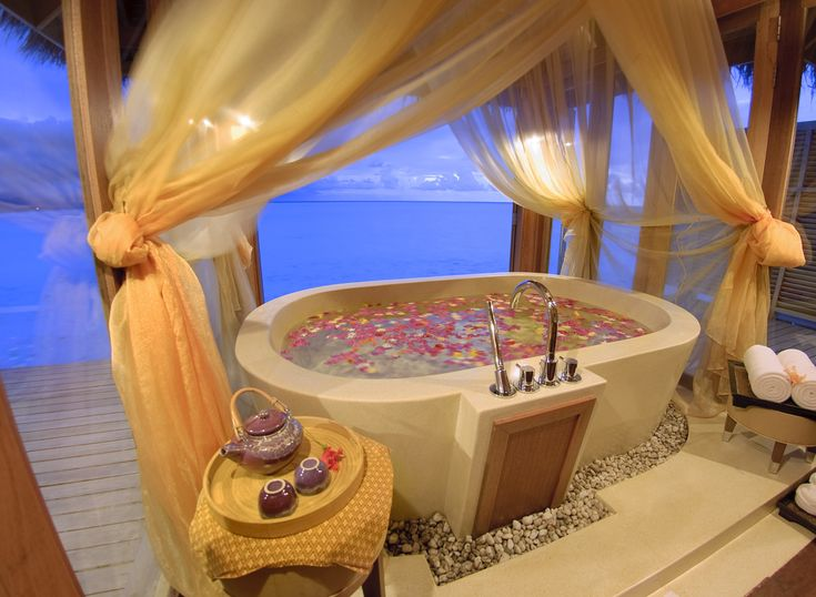 The Maldives and a romantic outdoor over water villa bungalow bathtub at the Anantara Dhigu