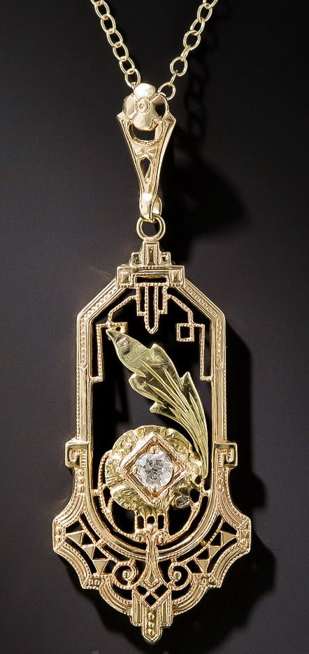 Art Deco Two-Tone Gold Diamond Pendant. An artful assemblage of Art Deco elements combine in this lovely 14 karat yellow gold pendant. A diamond set flower is accented with a green gold leaf flourish and framed in a geometric cartouche with filigree and beaded wire embellishments. A delicate tribute to the 1920's. The pendant measures 1 13/16 inches in length and 11/16 inch in width plus the bale. The pendant is strung on a delicate link chain measuring 16 inches long.