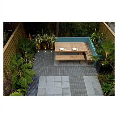 GAP Photos - Garden & Plant Picture Library - Elevated view of small urban garden with paved and cobblestone patio and built in seating area. Phormium in planters and raised beds with Dicksonia - Tree Ferns. London, UK - GAP Photos - Specialising in horticultural photography