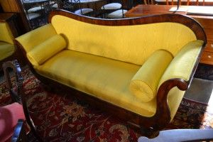 Africa then & now - Provenance Auction House: A 19th C Flame Mahogany Sofa. Curved back with conforming front, outswept arms, on straight base with outswept curved feet, upholstered back, sides and cushion in yellow silk with matching bulsters. 2000mm (width).