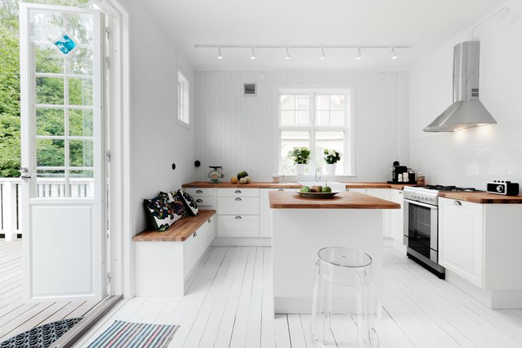 White & timber kitchen with bench seating.