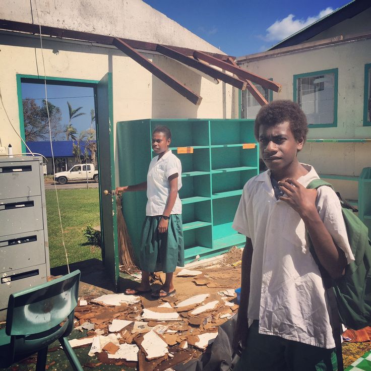 14-year-old Dawen and 15-year-old Joytracey from Port Vila. Vanuatu stand in what remains of their school library after it was destroyed by Cyclone Pam.