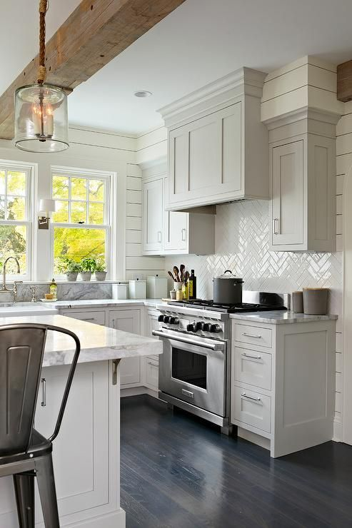 Stunning transitional kitchen features a stainless steel range sat against white herringbone backsplash tiles holding a light gray paneled hood flanked by light gray shaker cabinets fitted with polished nickel pulls and framed by ivory shiplap walls.