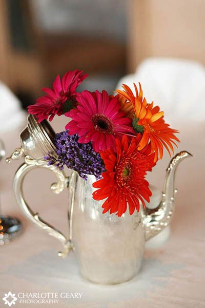 Centerpiece ideas. The birch stump, milk glass, potted plant, mixed shades of orange, and cowboy boot are cute...but the tea pot is my favorite!
