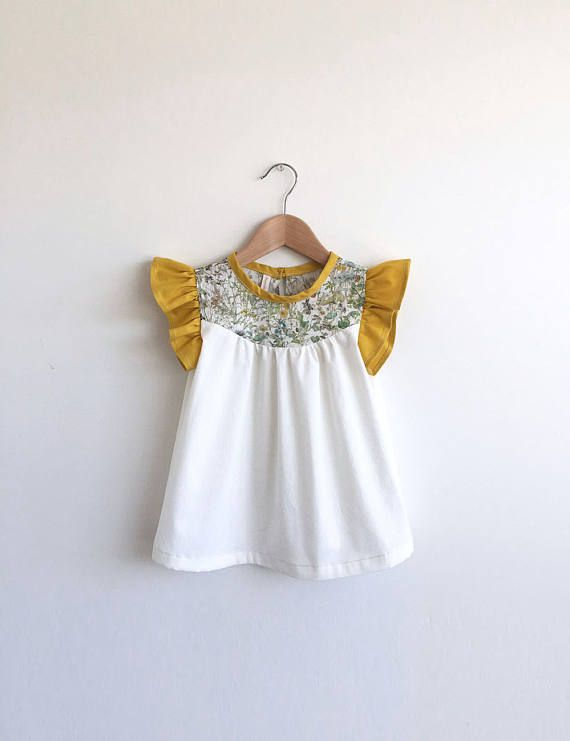 **THIS LISTING IS FOR DRESS LENGTH** 100% cotton dress with bodice made from off-white pima cotton, Liberty of London tana lawn floral print detail and gold flutter sleeves. Bias trim around neck with loop and button closure at back. *Please note: due to scale of print, placement will