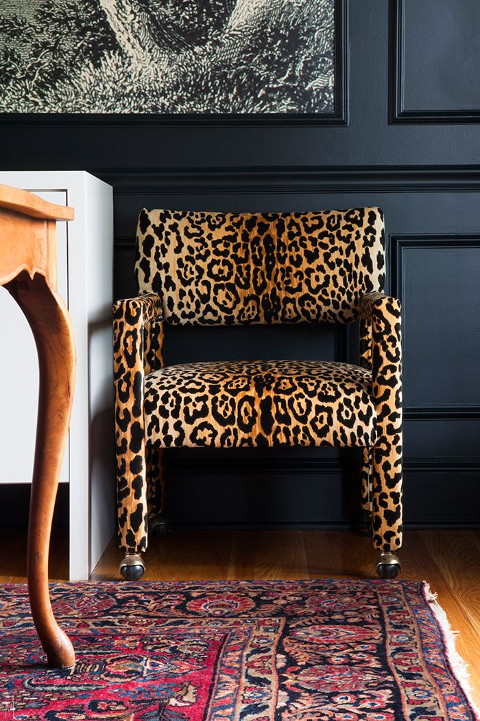 Dark walled dining room with leopard chairs and a vintage oriental.