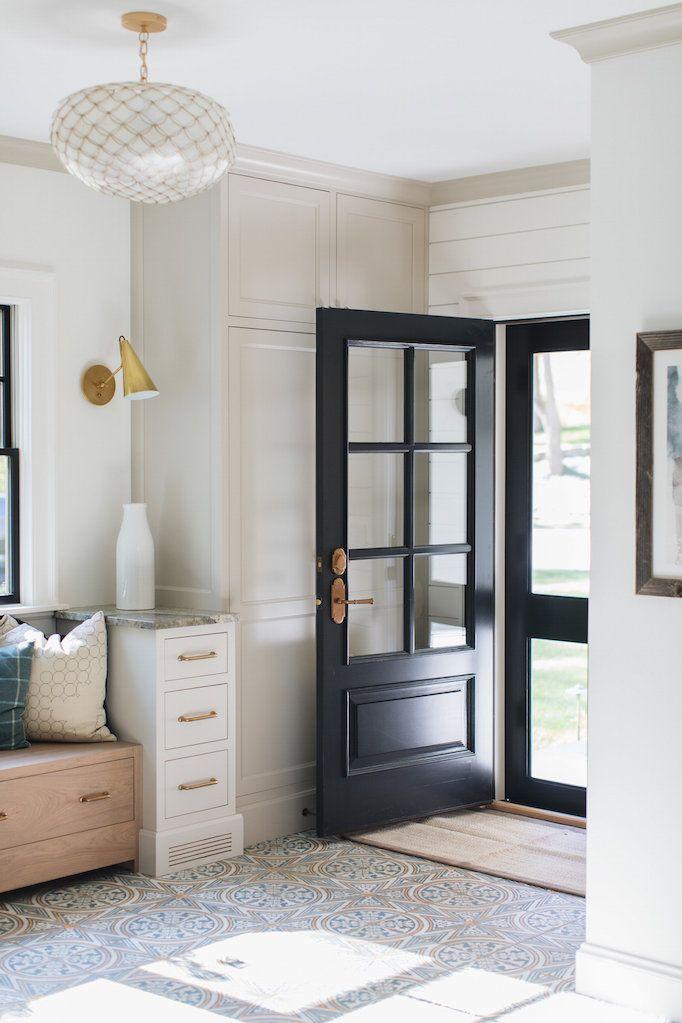 BECKI OWENS— Designer Spotlight: Jean Stoffer Design ❤️ Mudroom with capiz pendant, cement tile, black accents, midcentury brass sconce.
