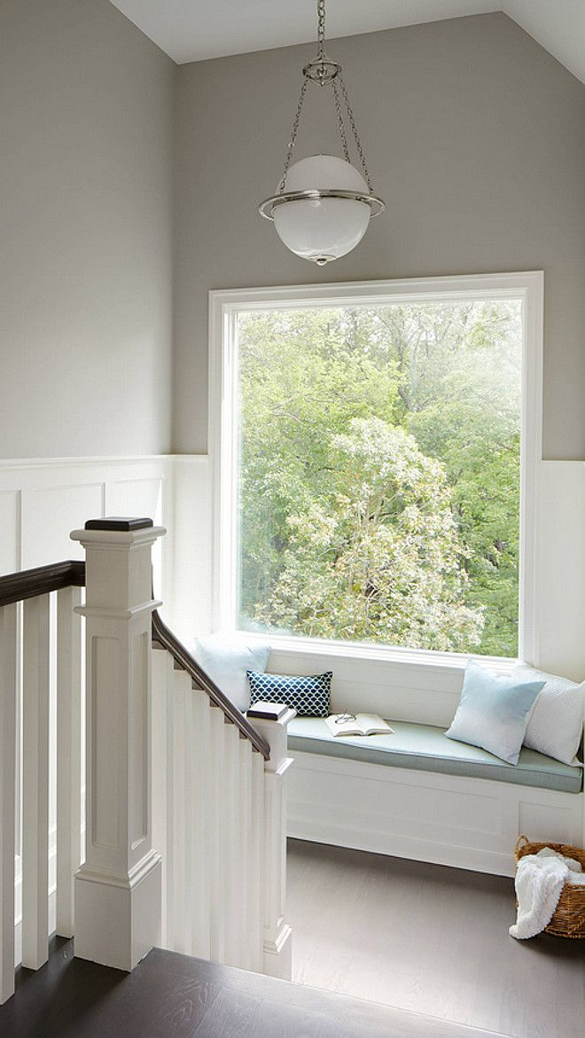 Beautiful landing with white rails, a built-in window seat, a large picture window and walls painted in Sherwin Williams Mindful Gray | Summit Signature Homes, Inc