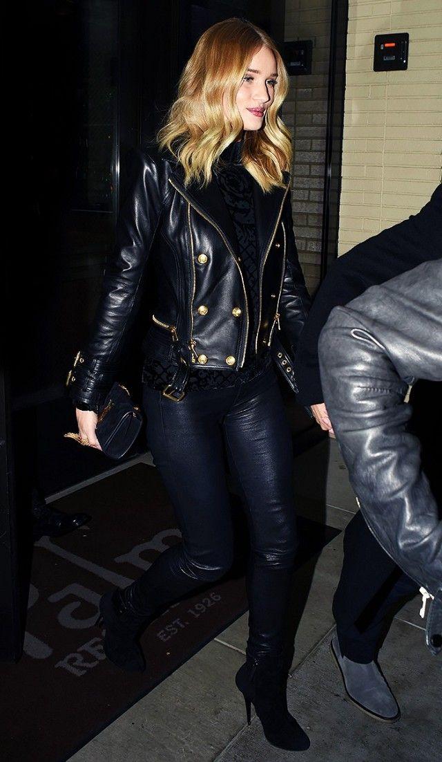 Rosie Huntington-Whiteley wears a black turtleneck, Balmain x H&M moto jacket, leather leggings, a Saint Laurent clutch, and boots