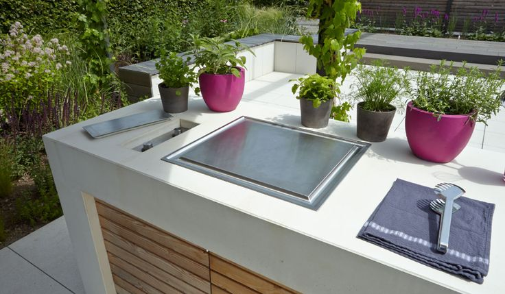 Die Outdoor-Gartenküche von #METTEN Stein+Design mit elektronischem Kochfeld, Spülbecken und großer Arbeitsfläche aus hellem, hochverdichtetem Beton.