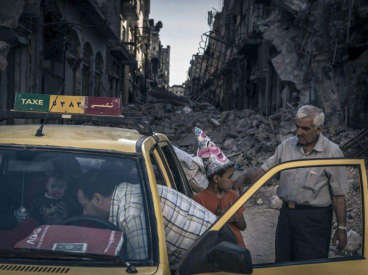Quartier d'Al-Khalidiya, Homs, Syrie, dimanche 15 juin 2014. Abu Hisham Abdel Karim et sa famille chargent leurs affaires dans un taxi. Spectacle étrange, des taxis circulent dans les rues désertes, parmi les décombres, pour aider les familles à récupérer ce qui reste de leur maison.