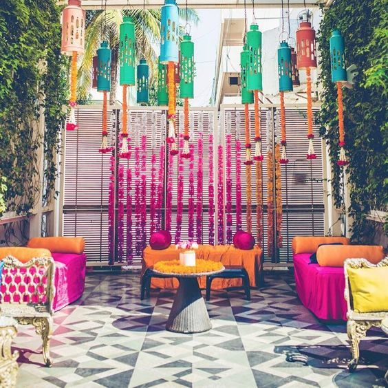 Kitschy and fun mehendi decor inspiration   Colorful hanging lanterns and flower chains   Marigold flower decor   Yellow and pink mehendi decor   DIY mehendi decor ideas   Styled by With Love Nilma   Every Indian bride's Fav. Wedding E-magazine to read. Here for any marriage advice you need   www.wittyvows.com shares things no one tells brides, covers real weddings, ideas, inspirations, design trends and the right vendors, candid photographers etc.