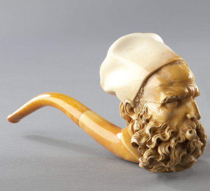 Pipe courbe en écume sculptée à décor de tête de Maure fumant la pipe, embout en ambre. XIXe siècle. Très belle patine de culotage. - Piasa - 18/09/2009