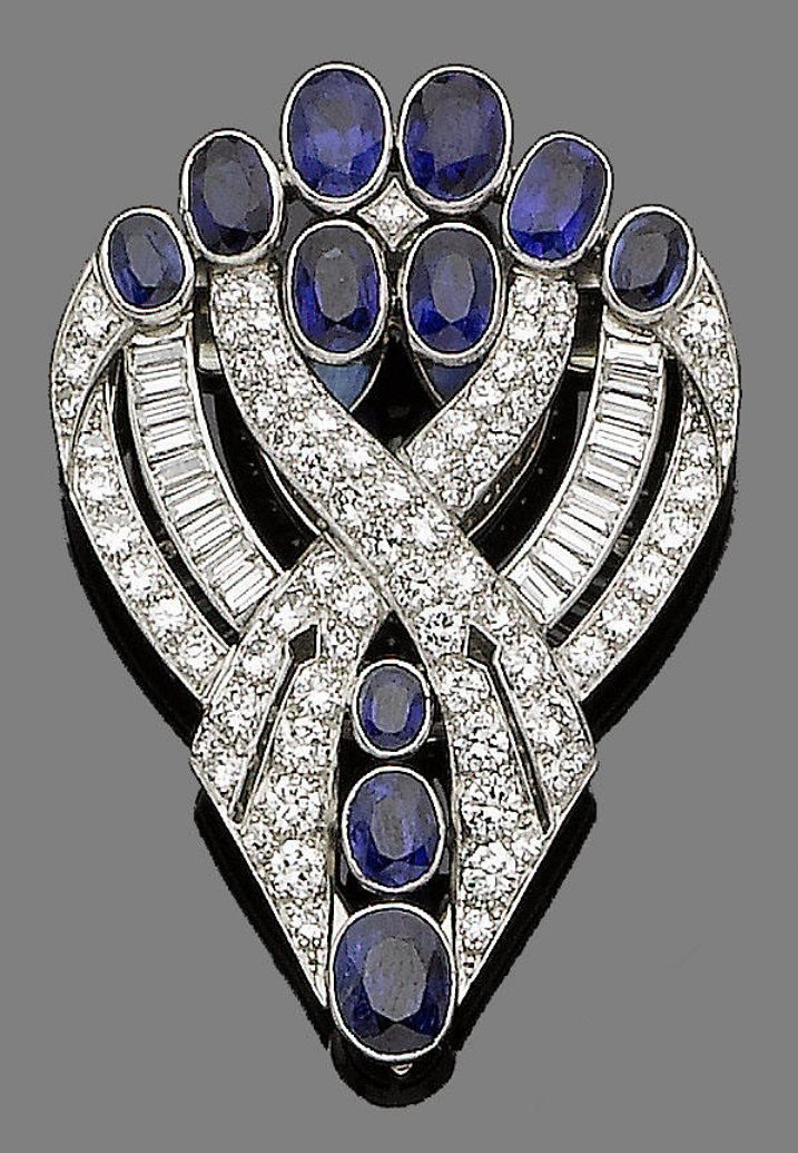 An art deco sapphire and diamond clip brooch, by J R Ogden & Sons, circa 1935.  The tapering openwork plaque of scrolling design collet-set with graduated oval-cut sapphires, brilliant and baguette-cut diamonds, diamonds approx. 2.85cts total, signed J R Ogden & Sons, length 4.9cm, fitted case